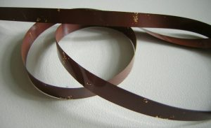 A typical non back coated tape, medium brown in color (can also be dark gray), showing significant shedding, where oxide has come off the tape in chunks